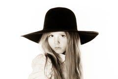 Kleines Mädchen, das wie ein Modell in Mutter ` s Hut aufwirft Stockbilder