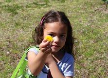 Kleines Mädchen, das wilde gelbe Blume hält lizenzfreies stockbild