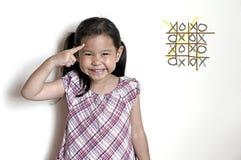 Kleines Mädchen, das an xo Spiel denkt lizenzfreie stockbilder