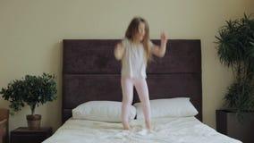 Kleines Mädchen, das zu Hause auf das Bett springt stock footage