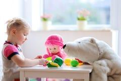 Kleines Mädchen, das zu Hause in der Vorschule oder spielt Stockbilder