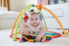 Kleines Mädchen, das zu Hause mit Spielwaren auf dem Boden spielt Lizenzfreies Stockfoto