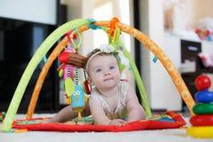 Kleines Mädchen, das zu Hause mit Spielwaren auf dem Boden spielt Lizenzfreie Stockfotos