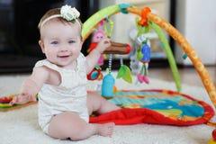 Kleines Mädchen, das zu Hause mit Spielwaren auf dem Boden spielt Stockbilder