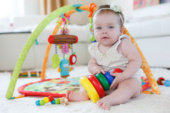 Kleines Mädchen, das zu Hause mit Spielwaren auf dem Boden spielt Stockfotos