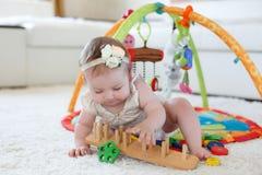 Kleines Mädchen, das zu Hause mit Spielwaren auf dem Boden spielt Stockbild