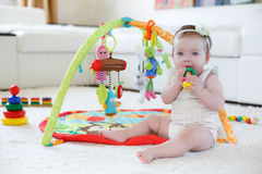 Kleines Mädchen, das zu Hause mit Spielwaren auf dem Boden spielt Stockfotografie