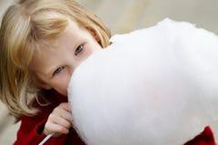 Kleines Mädchen, das Zuckerwatte isst Stockbild
