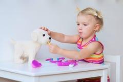 Kleines Mädchen, das zuhause Doktor spielt lizenzfreies stockbild