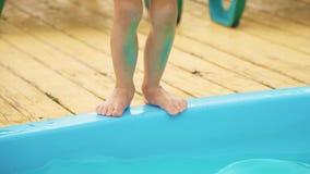 Kleines Mädchen, das zum Swimmingpool springt stock footage