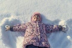 Kleines Mädchen, das zurück auf ihr im Schnee, Hand in Hand in Form eines Engels liegt Stockfotos