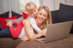 Kleines Mädchen, das zurück auf ihren Müttern liegt, während sie Laptop benutzt Stockbild
