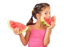 Kleines Mädchen, das zwei Scheiben Wassermelone isst Lizenzfreies Stockbild