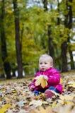 Kleines Mädchen in den Blättern Stockfotografie