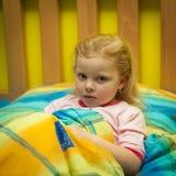 Kleines Mädchen in den Blättern auf einem hölzernen Bett Lizenzfreies Stockfoto