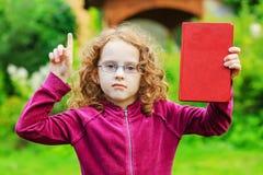 Kleines Mädchen in den Brillen mit roten Buch und dem Finger oben Lizenzfreie Stockbilder