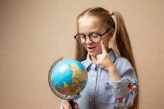 Kleines Mädchen in den Gläsern, die Kugel halten stockfoto