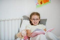 Kleines Mädchen in den Gläsern ein Buch beim Lügen lesend im Bett Lizenzfreie Stockfotos
