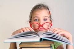 Kleines Mädchen in den Gläsern las Buch Stockbild