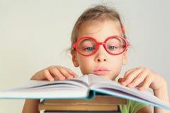 Kleines Mädchen in den Gläsern las Buch Stockbilder
