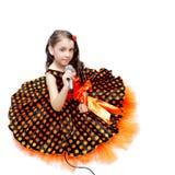 Kleines Mädchen in den orange Erbsen kleiden mit Mikrofon an Stockbild