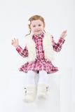 Kleines Mädchen in den Pelzstiefeln und -weste sitzt auf großem Würfel Stockfotografie