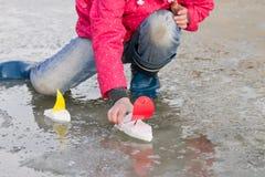 Kleines Mädchen in den Regenstiefeln, die mit Schiffen wässern spielen im Frühjahr, Pfütze Stockfotos