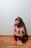Kleines Mädchen in der beiläufigen Kleidung schaut traurig in Verlegenheit zu bringen Lizenzfreies Stockbild