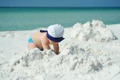 Kleines Mädchen in der blauen Kappe, die auf dem Strand spielt stockbild