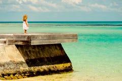 Kleines Mädchen der Einsamkeit, das den Ozean betrachtet Lizenzfreies Stockfoto