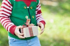 Kleines Mädchen in der Elfenstrickjacke und -hut, die auf ein Weihnachten im Holz warten lizenzfreies stockfoto