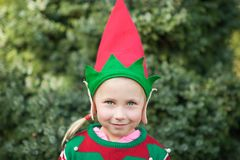 Kleines Mädchen in der Elfenstrickjacke und -hut, die auf ein Weihnachten im Holz warten Brustbild eines kleinen Kindes nahe dem  lizenzfreie stockfotos