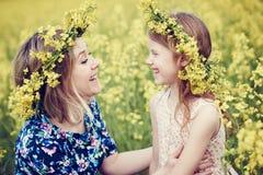 Kleines Mädchen der frohen Frau in der Blumengirlande am gelben Feld Stockfotos