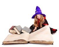 Kleines Mädchen der Hexe, das Buch hält. Stockfotos