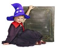 Kleines Mädchen der Hexe, das Buch hält. Stockfoto
