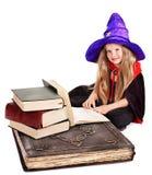 Kleines Mädchen der Hexe mit Stapelbuch. Lizenzfreies Stockfoto