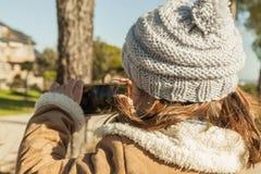 Kleines Mädchen der hinteren Ansicht, das Fotos mit einem Smartphone macht Stockbild