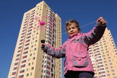 Kleines Mädchen in der Jacke, Spiele mit Propeller lizenzfreies stockfoto