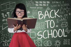 Kleines Mädchen in der Klasse, die ein Buch liest Lizenzfreies Stockfoto