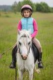 Kleines Mädchen in der Kleidung für eine Pferdsitzende Schärfe auf das Mädchen draußen reiten Stockfoto