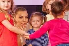 Kleines Mädchen der Lehrershow, das Finger in der Gruppe zeigt Stockfotografie