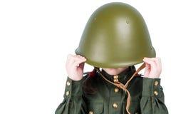 Kleines Mädchen in der Militäruniform, versteckt ihrem Kopf in einem Schutzhelm, Platz für Aufschrift, lokalisiert auf Weiß stockfoto