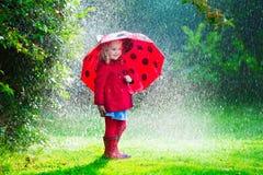 Kleines Mädchen in der roten Jacke, die im Herbstregen spielt Lizenzfreie Stockfotografie