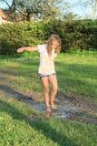 Kleines Mädchen in der schlammigen Pfütze Lizenzfreies Stockfoto