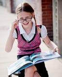 Kleines Mädchen in der Schuluniform und in den Gläsern Stockfotografie