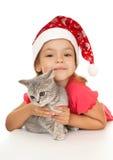 Kleines Mädchen in der Schutzkappe des neuen Jahres mit einem Kätzchen. Lizenzfreie Stockbilder