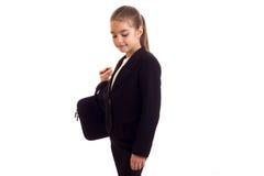 Kleines Mädchen in der schwarzen Jacke, die Diplomaten hält Stockfoto