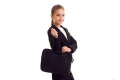 Kleines Mädchen in der schwarzen Jacke, die Diplomaten hält Lizenzfreie Stockbilder