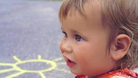 Kleines Mädchen der Seitenansicht sitzt auf dem Asphalt Weissen Sie gemalte Sonne ist auf dem Asphalt hinter ihrer Schulter Lizenzfreies Stockbild