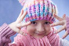 Kleines Mädchen in der Strickmütze, im Schal und im Handschuh Stockfoto